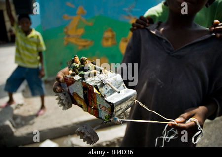 A young Haitian boy showing a home made armoured vehicle toy on the street of the slum of Cité Soleil. - Stock Photo