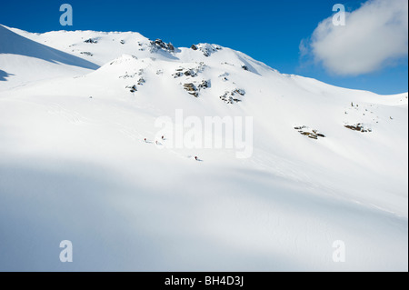 A group of skiers take a run down a large alpine bowl in the backcountry of the Selkirk Mountains, Canada. - Stock Photo