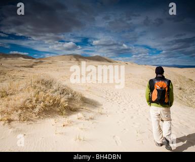 A man walks on natural sand dunes beneath a cloudy sky in Mojave Desert, California. - Stock Photo