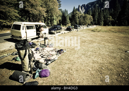 A man sorting rock climbing gear in front of a van in Yosemite National Park, California. - Stock Photo
