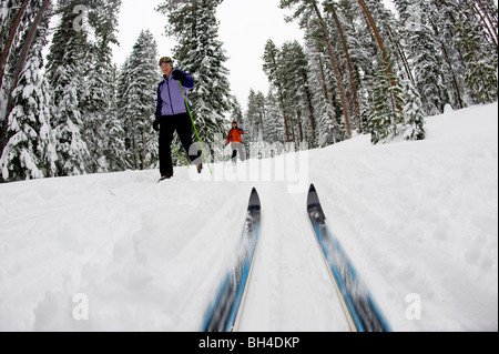 Low angle view of cross country ski tips and two young women nordic skiing on a cross country trail in the snow - Stock Photo