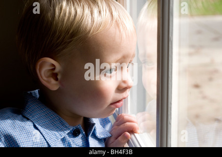 Little boy looking out a window - Stock Photo