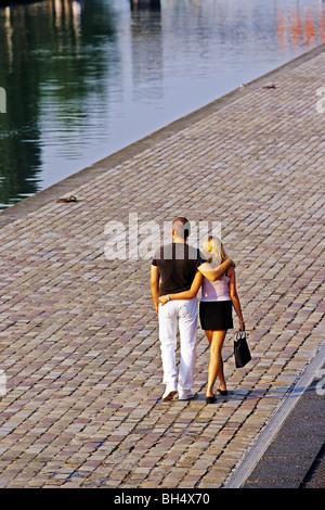 LOVERS WALKING ALONG THE OURC CANAL, WATERWAY IN THE PARC DE LA VILLETTE, PARIS (75), FRANCE - Stock Photo