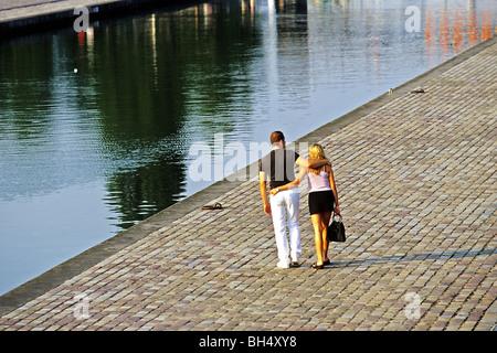 A COUPLE STROLLING ALONG THE OURCQ CANAL IN THE PARC DE LA VILLETTE, PARIS (75), FRANCE - Stock Photo