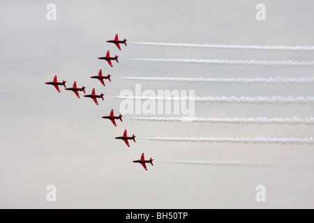 The famous Red Arrows display team flying in formation over Bournemouth Bay in August. - Stock Photo
