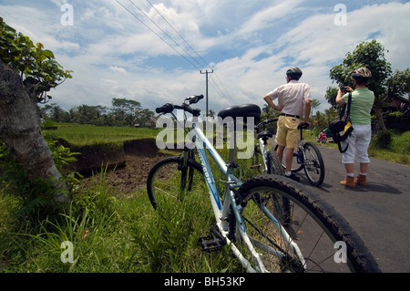 Middle-aged tourist couple pause for a photo on a bicycle tour in Bali, Indonesia. No MR or PR - Stock Photo
