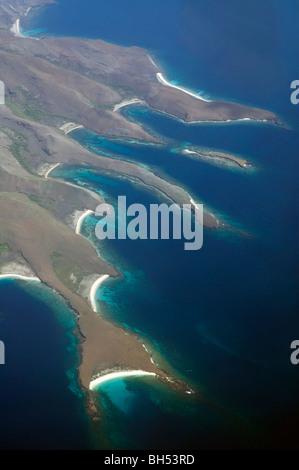 Aerial view of spectacular coastline and fringing coral reefs of Banta Island, Komodo Marine Park, Indonesia - Stock Photo