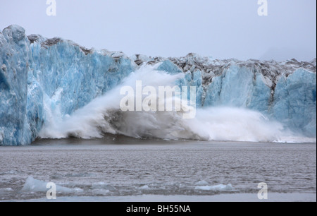 Glacier of blue ice calving into the ocean creating a huge splash and following wave - Stock Photo