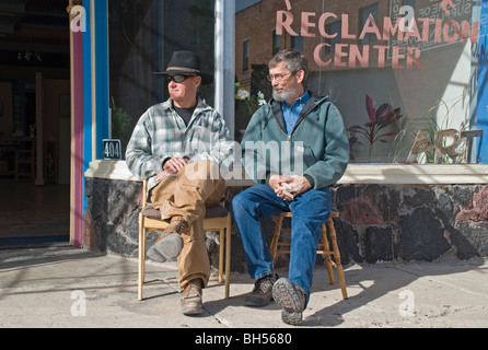 Two local men in Carrizozo enjoy the sunshine and watch passersby on a warm day in January. - Stock Photo