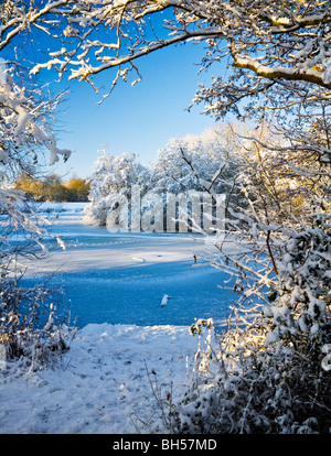 The frozen waters of a small lake known as Liden Lagoon in Swindon, Wiltshire, England, UK taken in January 2010 - Stock Photo