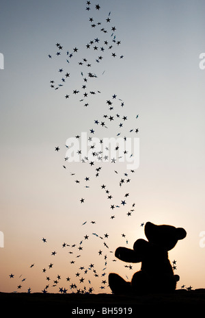 Teddy bear catching falling stars silhouette - Stock Photo
