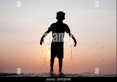 Indian boy dripping wet after having water thrown at him against an indian sunset. Silhouette. Andhra Pradesh, India - Stock Photo