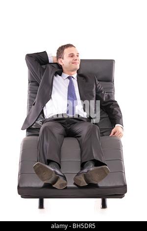 Businessman lying on a black leather sofa - Stock Photo