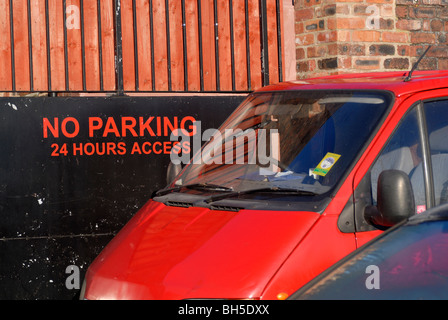 Vehicles parked in front of 'No Parking' sign. - Stock Photo