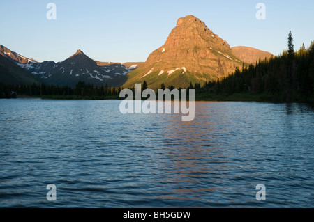 Sunrise light illuminates Sinopah Mountain with Pray Lake in foreground - Stock Photo