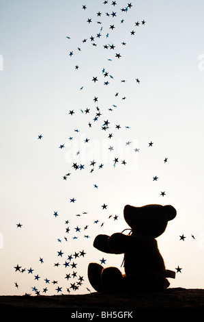 Teddy bear catching falling stars silhouette - Stock Photo