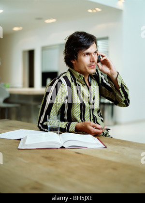Businessman talks on mobile phone - Stock Photo