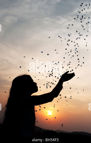 Silhouette of a young Indian girl catching falling stars at sunset. Andhra Pradesh, India - Stock Photo