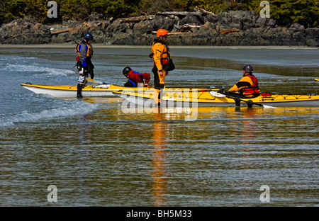 Sea kayakers negotiating light surf on MacKenzie Beach in Pacific Rim, Tofino, BC - Stock Photo