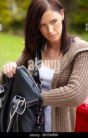 Woman looking in bag - Stock Photo