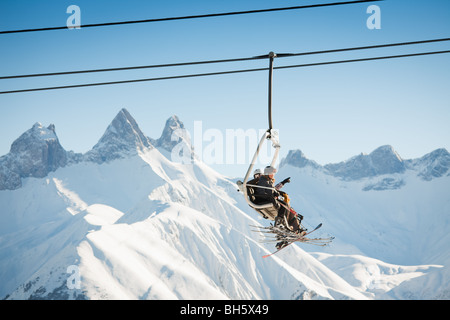 group of people on chairlift in France. Copy space - Stock Photo