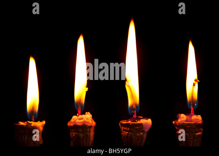 burning hanukkah candles in a menorah on black background - Stock Photo