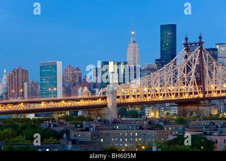 USA, New York, Manhattan skyline and Queensboro Bridge viewed from Queens - illuminated at dawn - Stock Photo