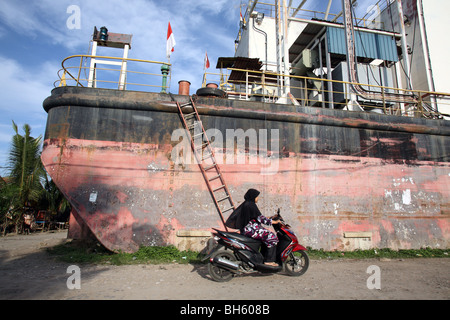Muslim woman on motorbike riding past the grounded electrical generator ship, PLTD Apung. Banda Aceh, Aceh, Sumatra, - Stock Photo