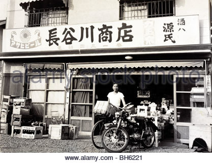 owner in front of the family grocery and liquor store Japan Yokosuka late 1950s - Stock Photo