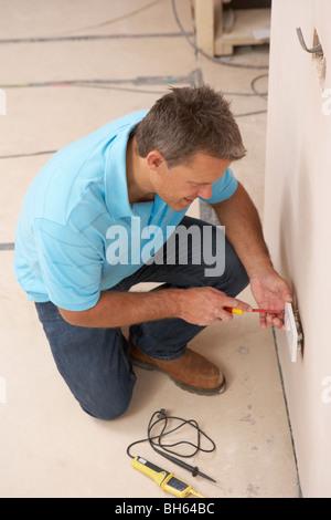 Electrician Installing Wall Socket - Stock Photo