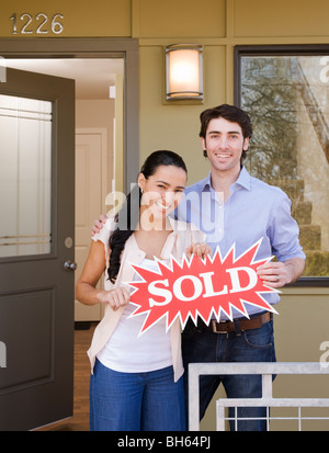 couple on front porch with sold sign - Stock Photo