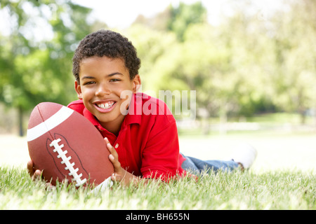 Boy In Park With American Football - Stock Photo
