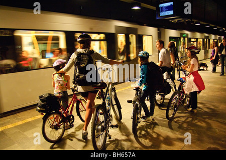 Family with bikes wait to board a metro train in Oslo, Norway - Stock Photo