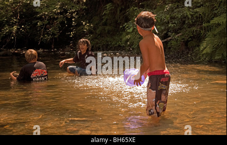 This boys are enjoying the local swimming hole with one throwing a bucket of water on the other two, catching them by surprise. Stock Photo