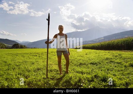 girl standing in pasture with scythe - Stock Photo
