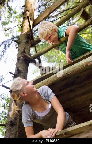 boy and girl climbing tree house - Stock Photo