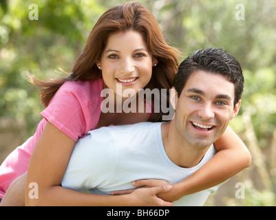 Young Man Giving Woman Piggyback Outdoors - Stock Photo