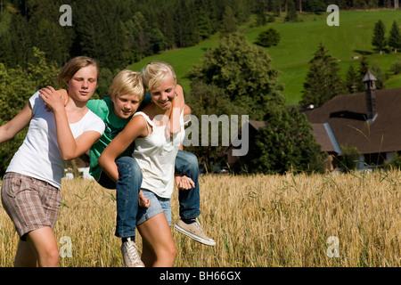 girls and boy walking along field - Stock Photo