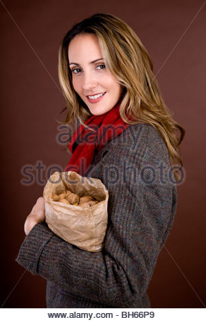 A mid adult woman holding a bag full of mixed nuts - Stock Photo
