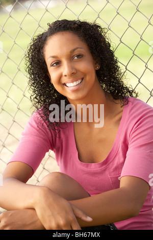 Teenage Girl Sitting In Playground - Stock Photo