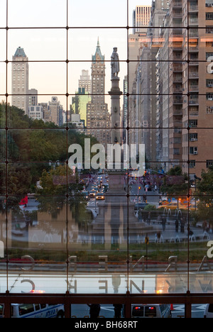 USA, New York City, Manhattan, Statue of Christopher Columbus in Columbus Circle viewed through a glass shopping - Stock Photo