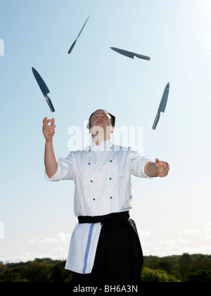 Chef juggling with knives - Stock Photo