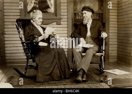 Elderly Couple Reading Mail on the Porch - Stock Photo