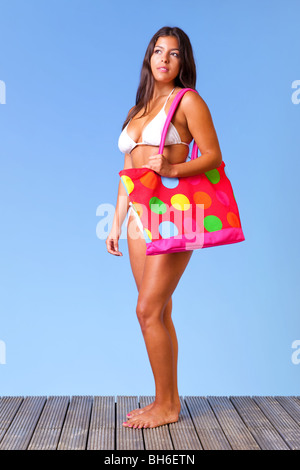 A woman wearing a white bikini carrying a colourful bag standing on decking against a blue sky. - Stock Photo