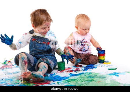 Two kids finger painting on white background - Stock Photo