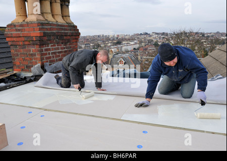 ... Roofers Spreading Adhesive Over Insulation For New EPDM Rubber Roofing  Membrane On House Flat Roof