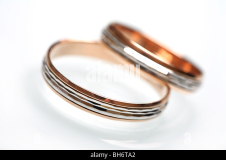 Wedding rings of yellow and white gold with diamond cut on white glass. - Stock Photo