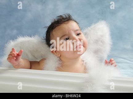 Hispanic baby girl with sad on her face and wearing angel wings in a studio - Stock Photo