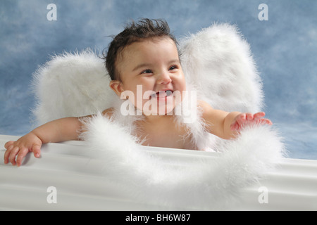 Hispanic baby girl with big smile look on her face and wearing angel wings in a studio - Stock Photo