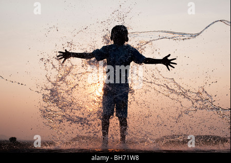 Indian boy having water thrown at him against an indian sunset. Silhouette. Andhra Pradesh, India - Stock Photo